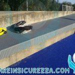Imbottitura di protezione su gradoni e muretto perimetrale in cemento armato in un campo da hockey su prato sintetico