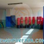 Pilastri con protezioni aderenti di colore blu applicate all'interno di una palestra di arti marziali